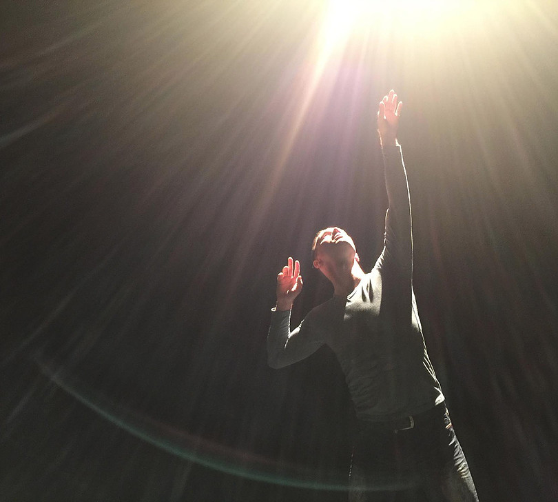 Actor/dancer Trevor Copp is looking up at a bright light