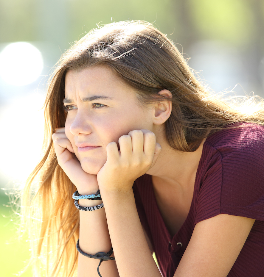 A teen girl sitting, her chin perched in her hands. She looks pensive.