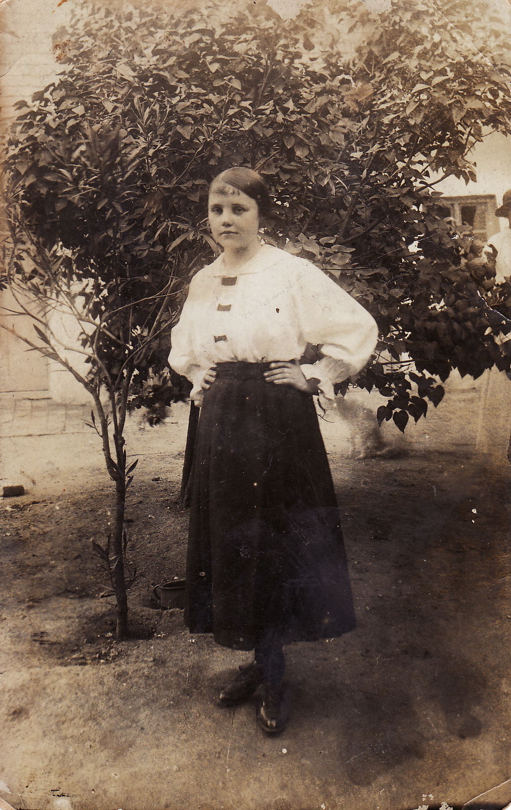 A young teenage girl wearing a white blouse and dark skirt and standing in front of a small tree. The photo is from the 1910s