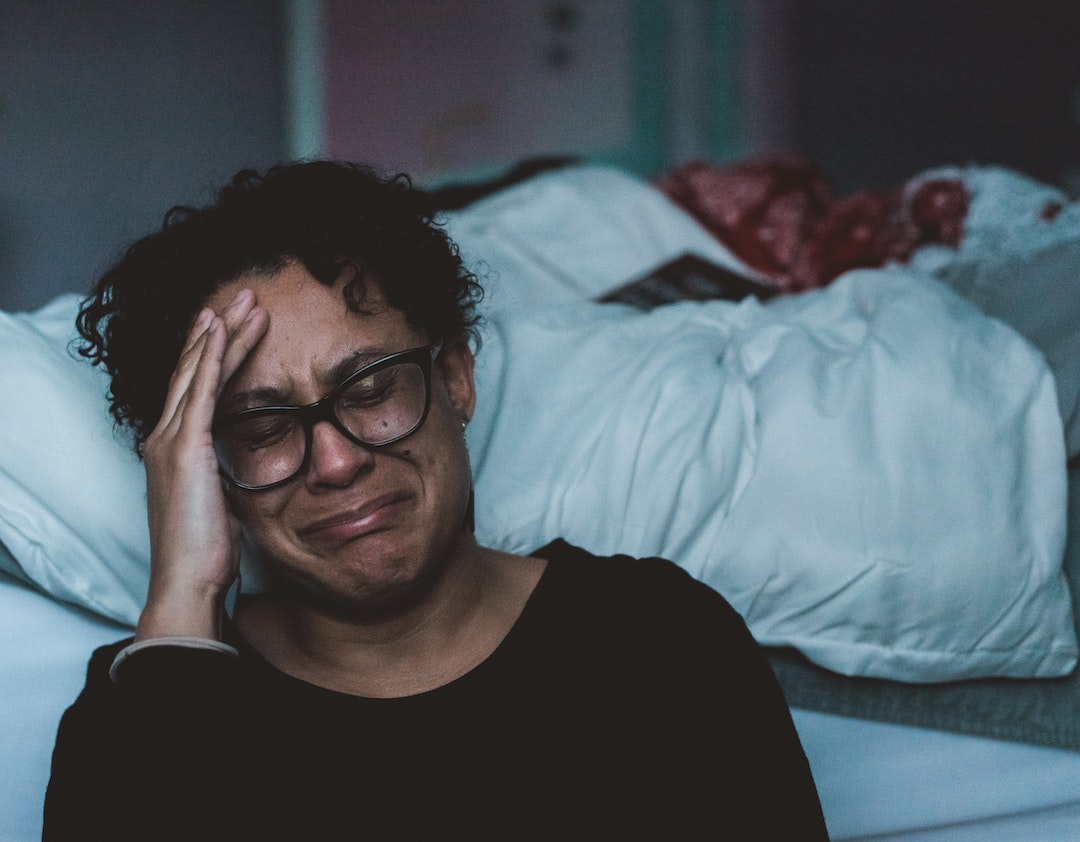 Woman crying, sitting against her bed.