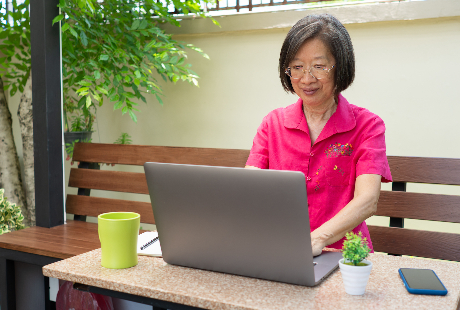 An Asian woman sitting at a computer, writing emails